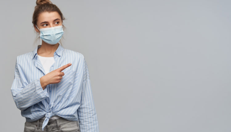 Charming girl with blond hair gathered in bun. Wearing striped knotted shirt and protective face mask. Pointing with index finger and watching to the right at copy space, isolated over grey background